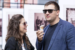 Smiling couple eating ice cream on the street. Beautiful couple smiling and eating ice cream on the street royalty free stock images