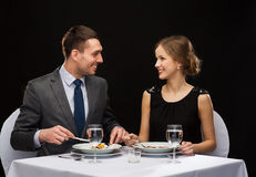 Smiling couple eating main course at restaurant Stock Images
