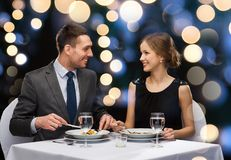 Smiling couple eating main course at restaurant Royalty Free Stock Photos