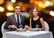 Smiling couple eating main course at restaurant Stock Photo