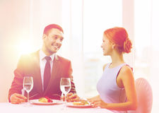Smiling couple eating main course at restaurant Stock Image