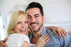 Smiling couple embracing each other in sofa Stock Images