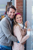 Smiling couple embracing and going window shopping Royalty Free Stock Photos