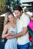 Smiling couple embracing and looking at smartphone Royalty Free Stock Photo