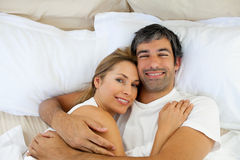 Smiling couple embracing lying in bed Stock Image