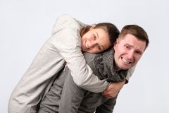 Smiling couple embracing in piggy back and looking at camera on white background royalty free stock photos