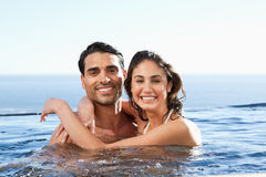 Smiling couple embracing in the pool Stock Images