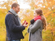 Smiling couple with engagement ring in gift box. Love, family, autumn and people concept - smiling couple with engagement ring in small red gift box outdoors royalty free stock photos