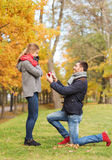 Smiling couple with engagement ring in gift box Royalty Free Stock Images