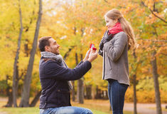 Smiling couple with engagement ring in gift box. Love, family, autumn and people concept - smiling couple with engagement ring in small red gift box outdoors Stock Images