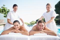 Smiling couple enjoying couples massage poolside stock photography