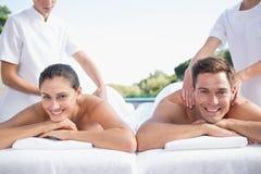 Smiling couple enjoying couples massage poolside Stock Photo
