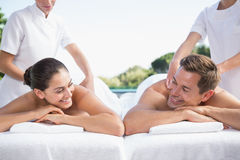 Smiling couple enjoying couples massage poolside