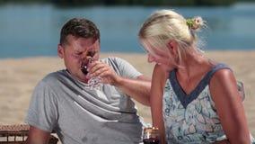 Smiling couple enjoying picnic on the beach stock video