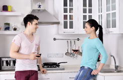 Smiling couple enjoying red vine in the kitchen Royalty Free Stock Images