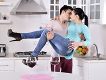 Smiling couple enjoying red vine in the kitchen Royalty Free Stock Photos