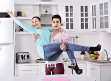 Smiling couple enjoying red vine in the kitchen Stock Photo