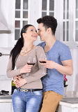 Smiling couple enjoying red vine in the kitchev Royalty Free Stock Photos