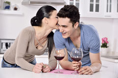 Smiling couple enjoying red vine in the kitchev royalty free stock image