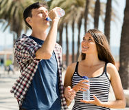 Smiling  couple enjoying  water from plastic bottles Royalty Free Stock Image