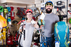 Smiling couple examining climbing equipment items Royalty Free Stock Photography