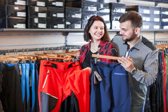 Smiling couple examining touristic trousers Stock Images