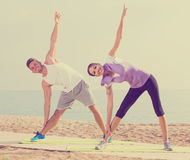 Smiling couple exercising yoga poses standing on beach. Smiling couple exercising yoga poses standing on sunny beach by ocean in morning Royalty Free Stock Photography