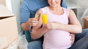 Smiling couple expecting a baby drinking on floor Royalty Free Stock Photos