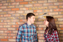 Smiling Couple Facing Each Other near Brick Wall Royalty Free Stock Photography