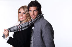 Smiling couple of fashion models. Couple of fashion models wearing winter dress and scarf. Studio shot Royalty Free Stock Photos