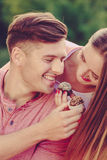 Smiling couple feeding each other. Royalty Free Stock Images