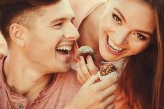 Smiling couple feeding each other. Stock Photo