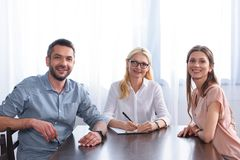 Smiling couple and female counselor writing in clipboard at table. In office royalty free stock photography