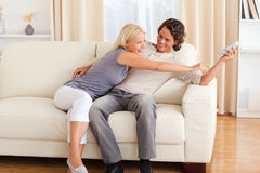 Smiling couple fighting for the remote Stock Photos