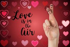 Smiling couple fingers with love message. Against digitally generated background Stock Image