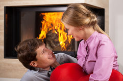 Smiling couple by fireplace Royalty Free Stock Images