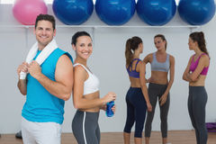 Smiling couple with fitness class in background Stock Images