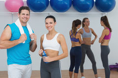 Smiling couple with fitness class in background Royalty Free Stock Image
