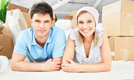 Smiling couple on the floor after unpacking boxes Royalty Free Stock Photo