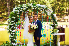 Smiling couple in flower arch. On nature Royalty Free Stock Photo