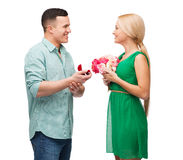 Smiling couple with flower bouquet and ring Stock Images