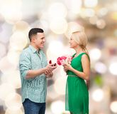 Smiling couple with flower bouquet and ring. Happiness, holidays, celebration and couple concept - smiling couple with flower bouquet and ring in a box Royalty Free Stock Photography
