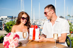 Smiling couple with gift box cafe Stock Photography