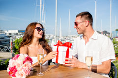 Smiling couple with gift box cafe Royalty Free Stock Images