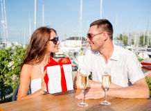 Smiling couple with gift box cafe Royalty Free Stock Image