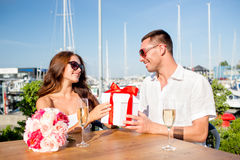 Smiling couple with gift box cafe Royalty Free Stock Photos
