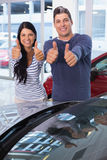 Smiling couple giving thumbs up Stock Image