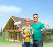 Smiling couple in gloves with paint rollers Stock Photos
