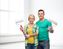 Smiling couple in gloves with paint rollers Stock Images