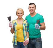 Smiling couple in gloves with spatula Royalty Free Stock Photo
